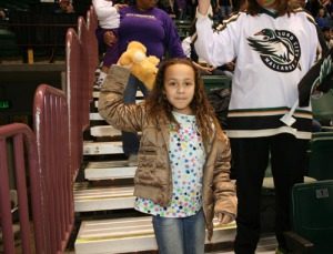 A young fan prepares to toss a teddy bear onto the ice.